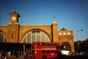 A red Routemaster bus passes along Euston Road in front of Kings Cross Station, 1983